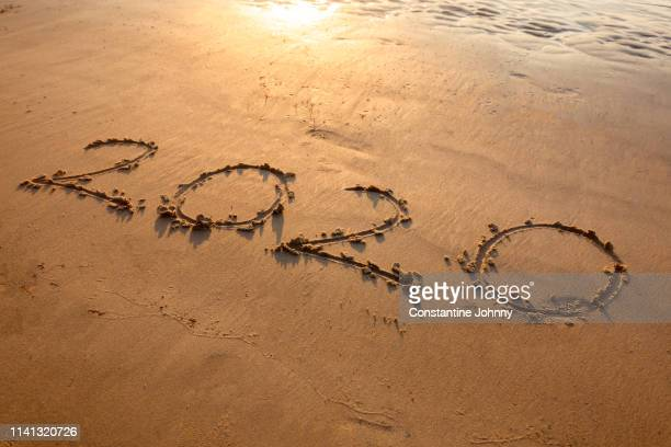 new year 2020 written on beach at sunset - dia de ano novo imagens e fotografias de stock