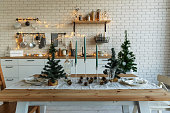 New Year and Christmas. Festive kitchen in Christmas decorations. Candles, spruce branches, wooden stands, table laying.