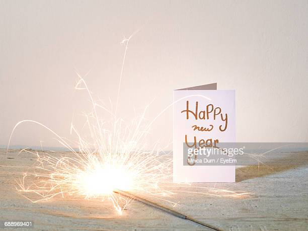 New Year Card With Lit Sparkler On Table Against Wall