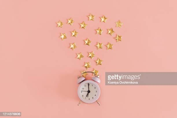 new year christmas top view flat lay black alarm clock twelve covered golden stars confetti copy space millennial pink color paper background minimal style template feminine blog social media postcard - 真夜中 ストックフォトと画像