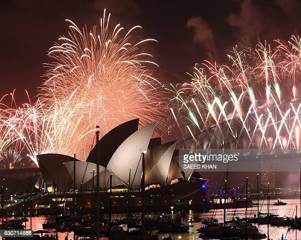 New Year fireworks illuminate the sky over the iconic Opera House and Harbour Bridge in Sydney on January 1 2017 / AFP / SAEED KHAN