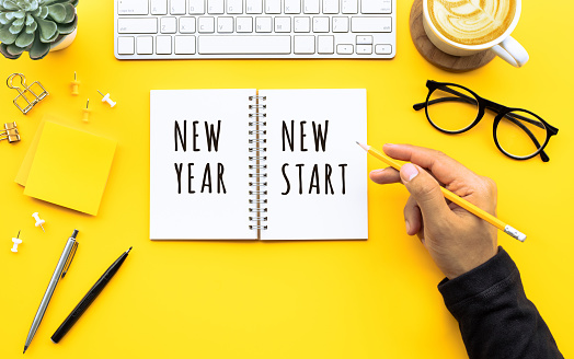 New year new start text with youngman writing on notepad on color desk table.Business goal-plan-action and resolution concepts 1173599469