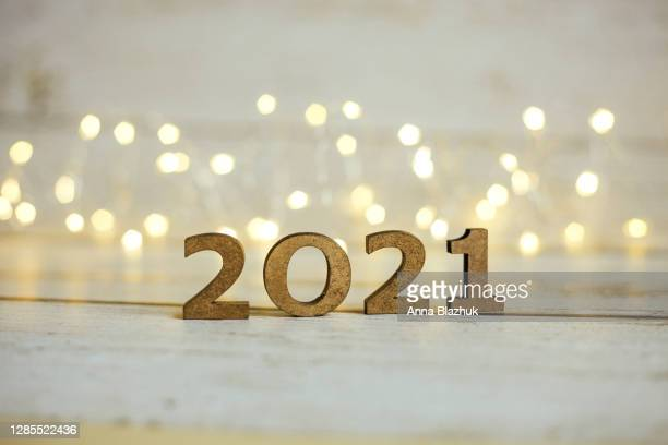 2021 new year number. festive card with blurred fairy lights and white shiny background. - 2021 stock pictures, royalty-free photos & images