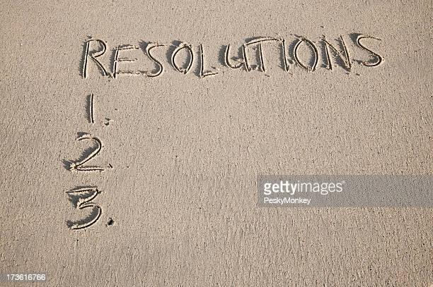 New Year Resolutions Written in Sand on Smooth Beach