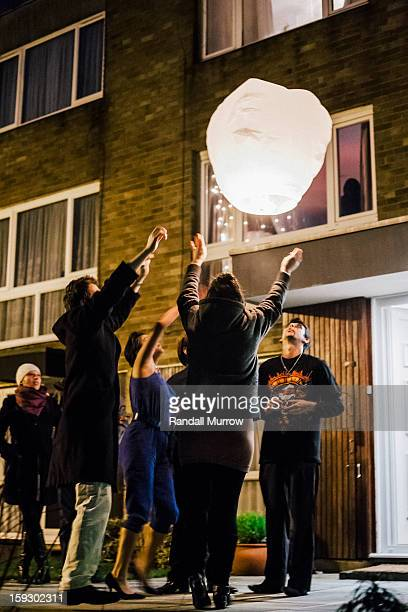 CONTENT] New year revellers in the UK light and release a chinese paper lantern into the sky outside their flat