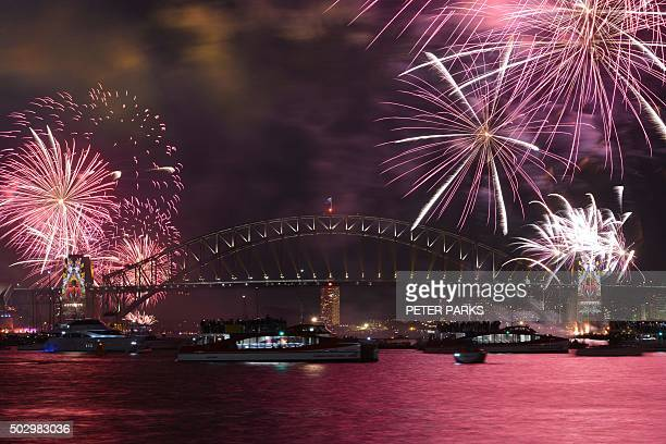 TOPSHOT New Year's Eve fireworks illuminate Sydney's iconic Harbour Bridge during the traditional early family fireworks show held before the main...