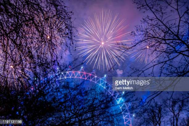 New Years Eve fireworks light up the Millennium Wheel from St James's Park on the 1st January 2020 in London in the United Kingdom