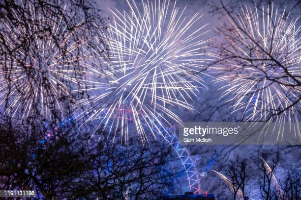 New Years Eve fireworks light up the Millennium Wheel from St James's Park on the 1st January 2020 in London in the United Kingdom.