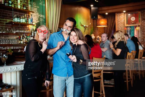 new years eve in a bar between group of coworkers and colleagues doing photo booths - 25 29 years photos stock photos and pictures