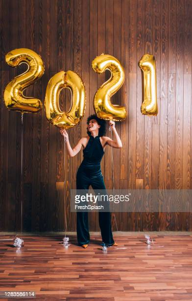 new year's eve party: a happy woman celebrating new year by dancing under 2021 golden balloons - new year stock pictures, royalty-free photos & images