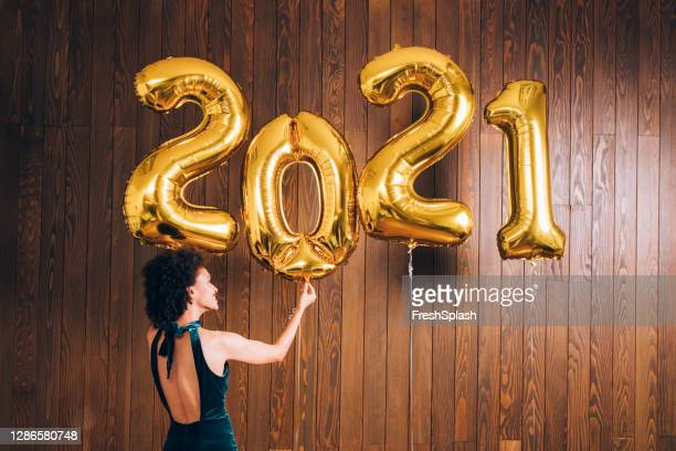 new year's eve party: happy african american woman decorating the room with huge '2021' golden balloons - embellished dress stock pictures, royalty-free photos & images