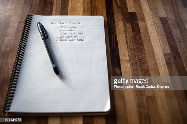 new year's resolution written on a notebook, and a pen on a wooden table - list stock pictures, royalty-free photos & images