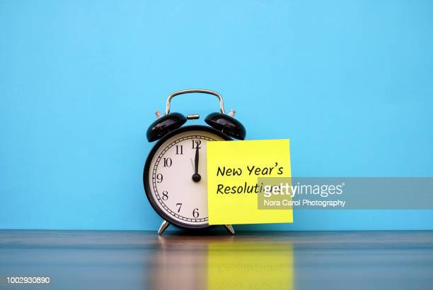 New Year's Resolutions Text on Adhesive Note Attached to Alarm Clock