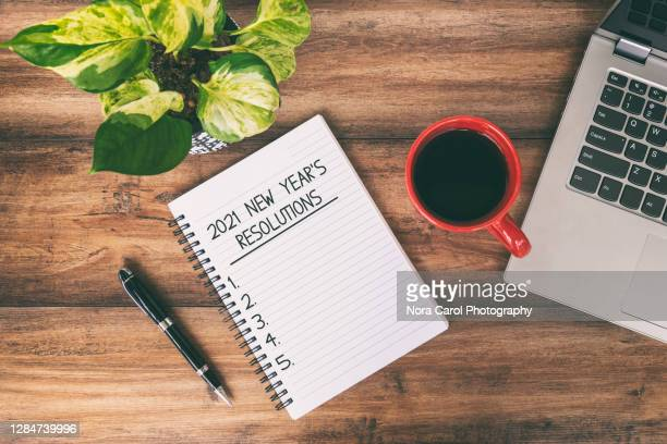 2021 new year's resolutions text written on notepad with laptop and cup of coffee on top of wooden desk - list stock pictures, royalty-free photos & images