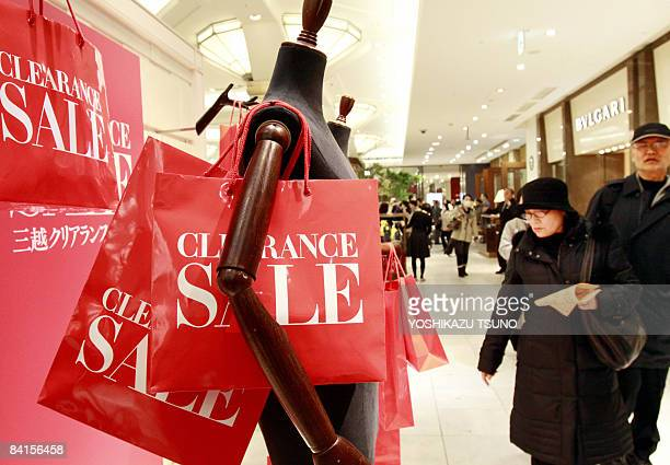 New Year's shoppers check lucky bags which contain items worth four times as much as the price tag to celebrate New Year business at Tokyo's...
