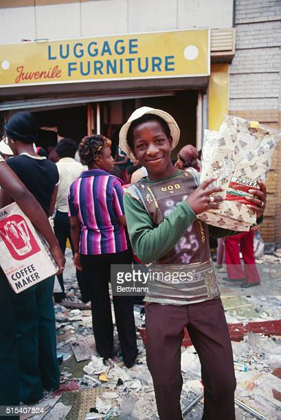 A young looter holds up a pair of pajamas he has taken from a store in the Bushwick section of Brooklyn after massive power failure in New York