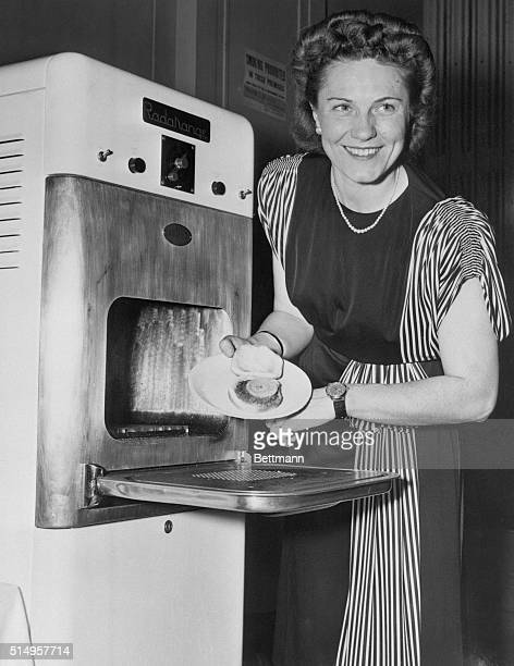 Anita Howarth is shown removing a well cooked hamburger sandwich fifteen seconds after it was placed in the new Raytheon Radarange during a...