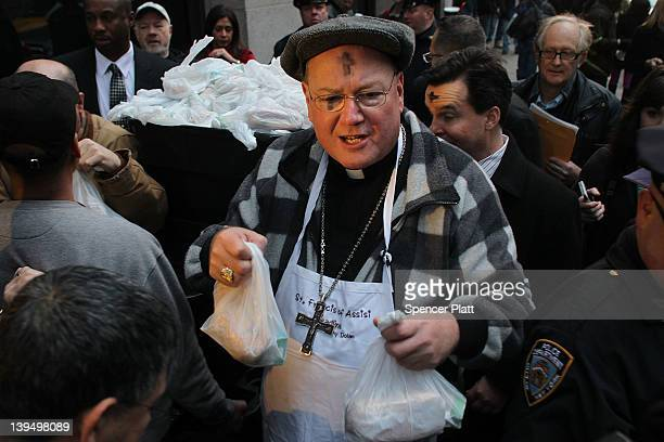 New York Archbishop Timothy Dolan joins fellow volunteers distributing food at a breadline at St Francis Assisi on Ash Wednesday on February 22 2012...