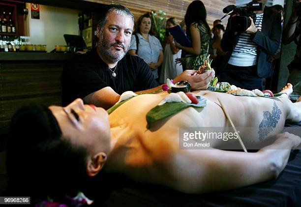 New York artist Spencer Tunick poses whilst standing over a model dressed only with sushi aT a press conference at the Toko Restaurant Bar on...