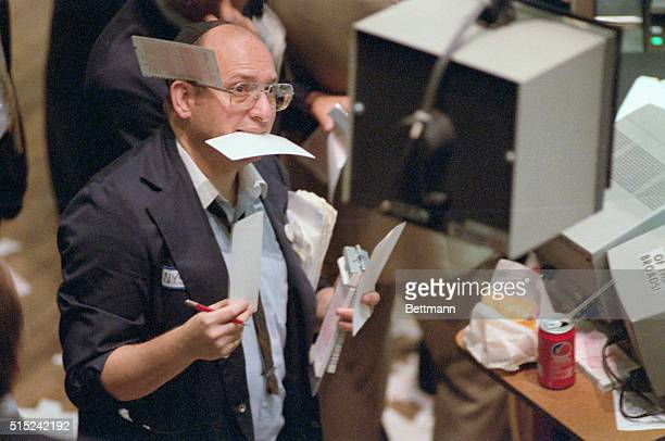As busy as a beaver once again 9/12 a floorman at the New York Stock Exchange takes orders during record volume day that saw the Dow Jones industrial...