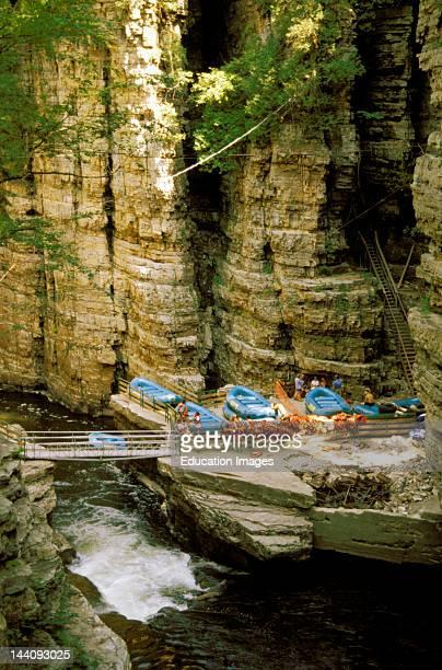New York Ausable Chasm Boats Along Ledge Of Creek Rocks And Cliffs Surrounding Bridge