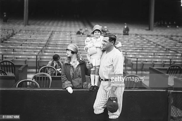 New York: Babe Ruth with wife and baby daughter, Dorothy whom he is kissing before game at the Yankee Stadium.