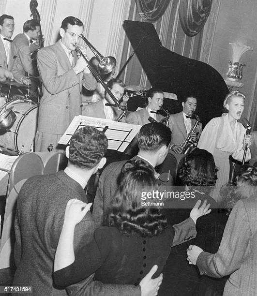 Bandleader Glenn Miller and his orchestra performing for the Chesterfield Radio Show ca 19401941 People stop dancing to listen to female singer...