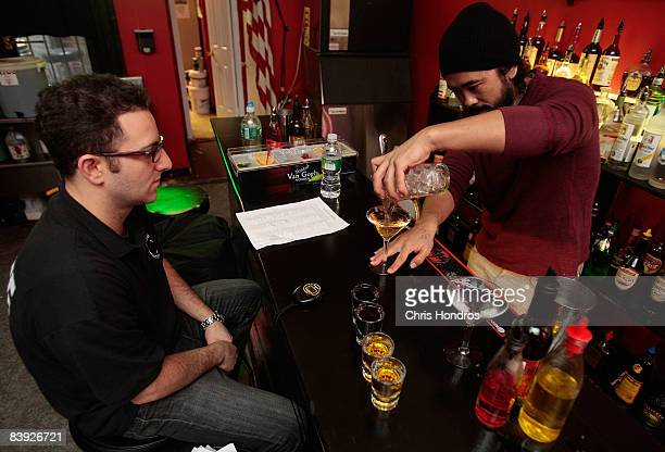 New York Bartending School student Mitsu Lowe is watched by instuctor Max Shulman as he makes 20 drinks in less than six minutes for his final exam...
