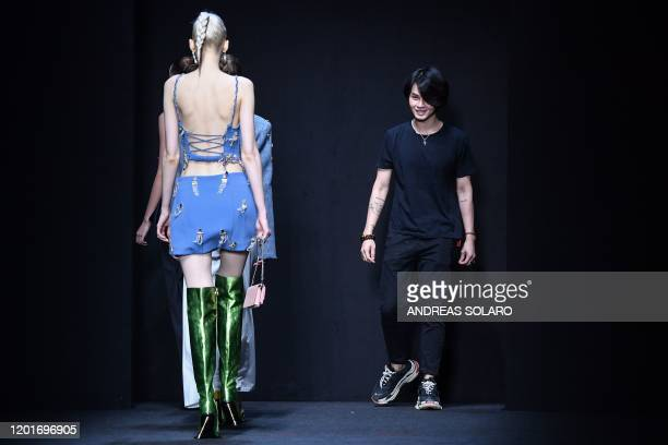 New York based Chinese designer Han Wen acknowledges applause following the presentation of the China We are With You fashion show kicking off the...