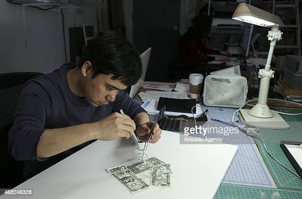 New York based Japanese artist Yuken Teruya works to make a tree made in money for his 'The Simple Truth' exhibition are displayed at Josée Bienvenu...