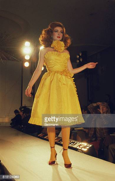 Bill Blass presents this strapless yellow taffeta short dance hall dress edged in taffeta pleats with a pleated taffeta rose at the neck as part of...