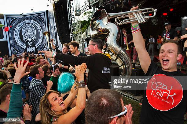 New York Brass Band playing in front of Shepard Fairey Obey posters in the Hell arena Shangri La field Glastonbury Festival 2016 The Glastonbury...