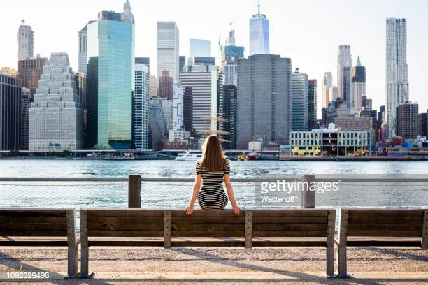 usa, new york, brooklyn, back view of woman sitting on bench in front of east river and skyline of manhattan - front view photos et images de collection