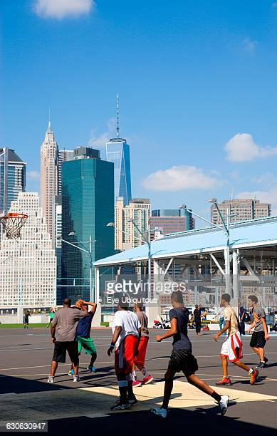 USA New York Brooklyn Bridge Park basketball courts on Pier 2 with Lower Manhattan skyscraper skyline beyond