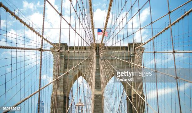 usa, new york, brooklyn, close up of brooklyn bridge metal cables and arches with american flag on the top - brooklyn bridge stock pictures, royalty-free photos & images