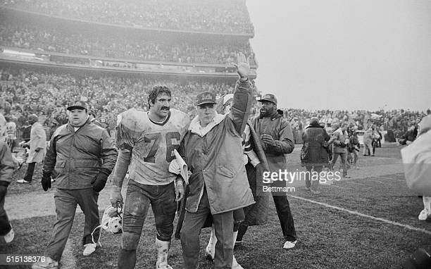 Buffalo coach Chuck Knox waves to Jet coach Walt Michaels across the field after the Bills defeated the Jets in the playoff opener December 27th t...