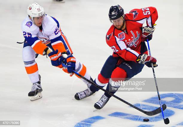 New York center Brock Nelson left and Washington defenseman Mike Green compete for the puck as the Washington Capitals play the New York Islanders in...
