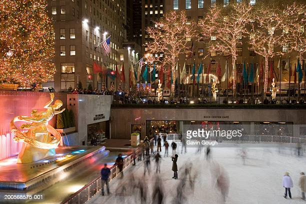 usa, new york, central park, people on ice rink (blurred motion) - new york city christmas stock photos and pictures