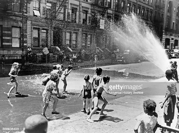 New York Children escape the heat of the East Side by using fire hydrant as a shower bath Photographer Roger Smith June 1943
