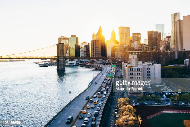 New York City aerial view skyline with Brooklyn Bridge and highway during sunset, NY, United States