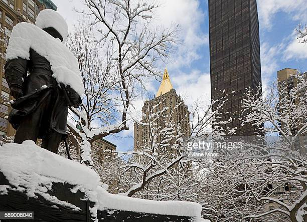 New York City after a snow storm Statue and the golden pyramid of the New York Life Insurance building rising above Madison Square park Snow covered...