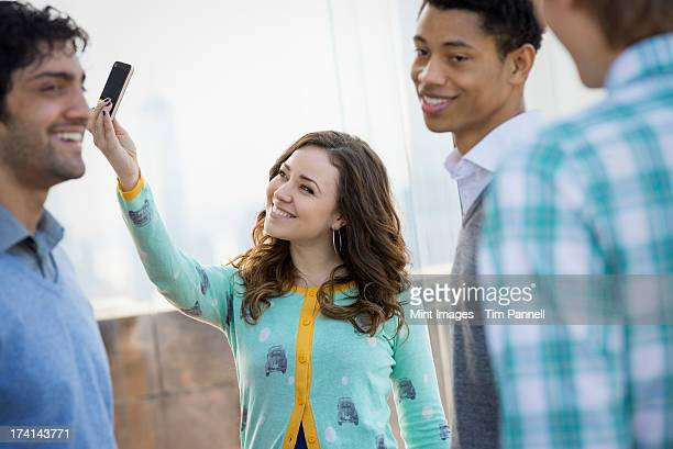 New York City. An observation deck. A woman using a smart phone to take an image. Three young men.