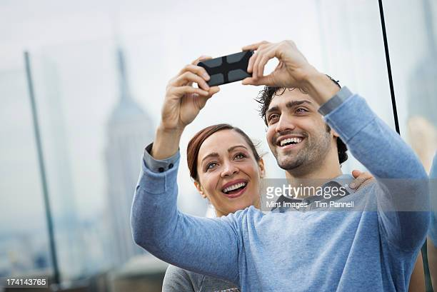 New York City. An observation deck. A young couple taking photographs with a mobile phone.
