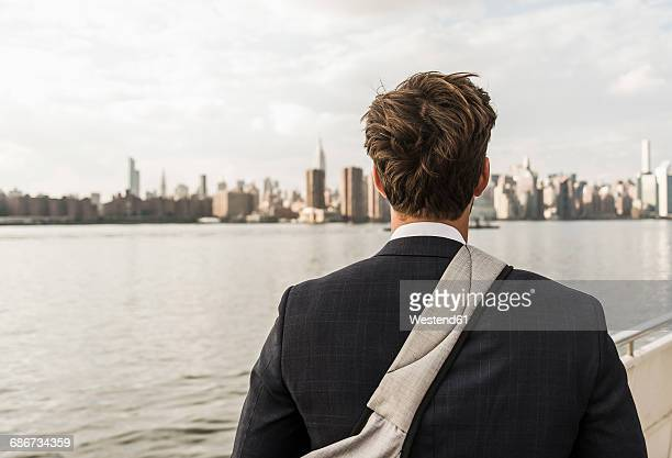 USA, New York City, back view of man at East River looking on Manhattan