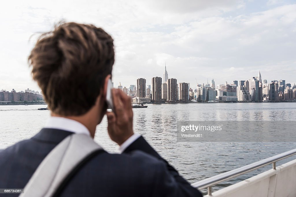 usa new york city back view of man on the phone with skyline of