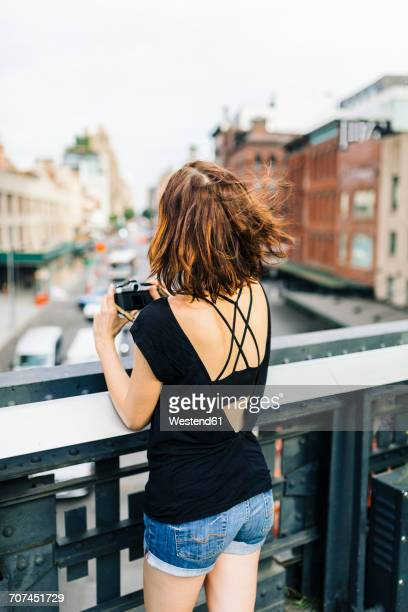 USA, New York City, back view of woman with camera on the High Line in Manhattan