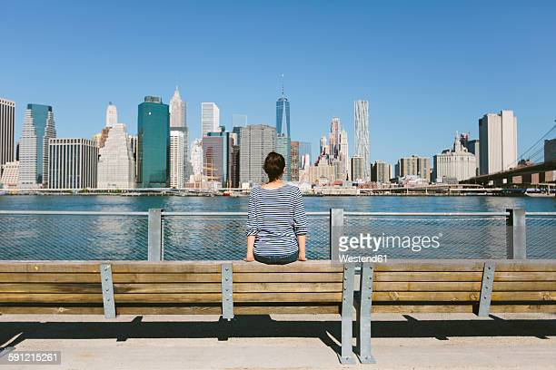 USA, New York City, back view of young woman looking at skyline