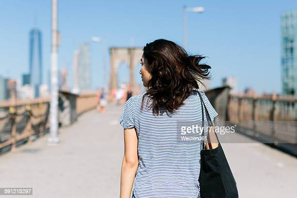 usa, new york city, back view of young woman walking on brooklyn bridge - mensch im hintergrund stock-fotos und bilder