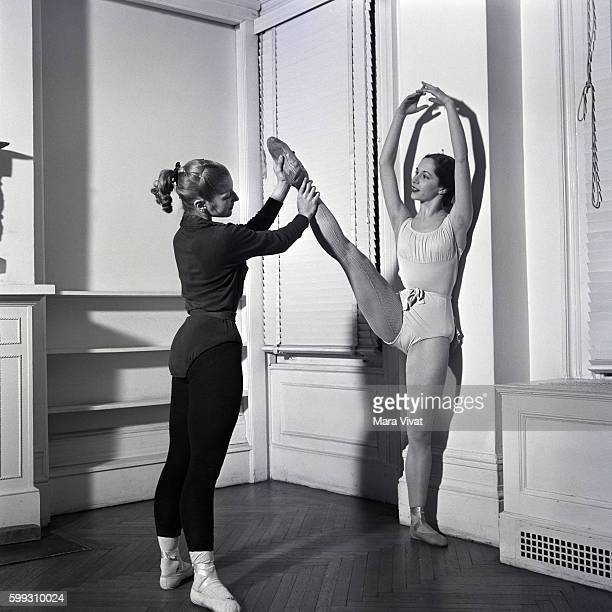 New York City Ballet dancer stretches her legs with assistance from a fellow dancer at a barre in the rehearsal studio New York City New York USA