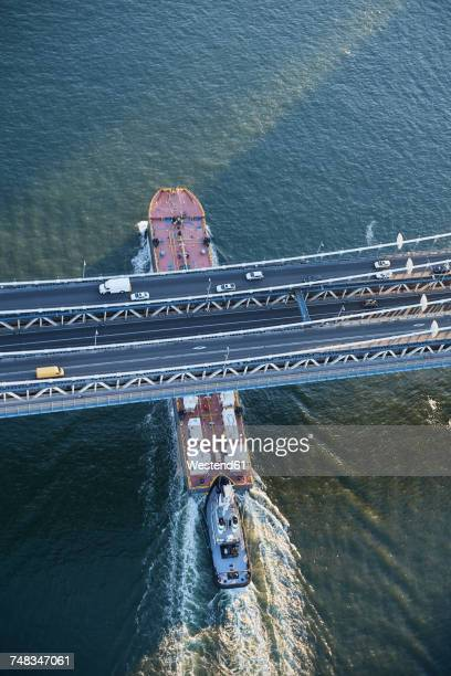 USA, New York City, barge sailing underneath Manhattan Bridge on East River, aerial view